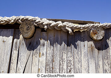 detail of a wooden cabin roof with rope
