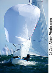 Sailboat - The white sails of a boat harness the power of...