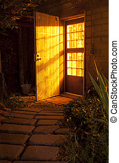 Door at night with light shining outside casting shadows on...