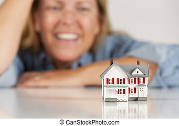 Smiling Woman Behind Model House on a White Surface