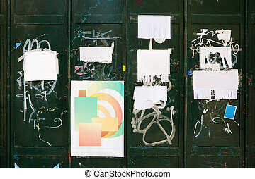 Grungy background - old torn posters and small private paper advertisements on green metal wall