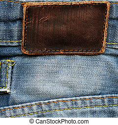 Highly detailed closeup of blank grungy brown leather label on vintage light blue stained denim with yellow seams, good for background