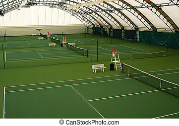 Indoor tennis court covered with a green coating