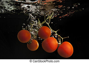 Tomatoes in water - Tomatoes dropped into water in front of...