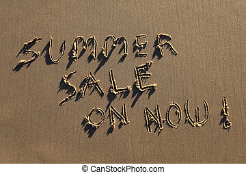 Summer Sale On Now written in the sand at the beach