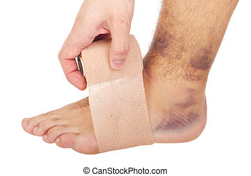 Bandaging a sprained ankle - young male with sprained ankle...