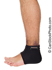 Ankle sprain support - young male with ankle support to...