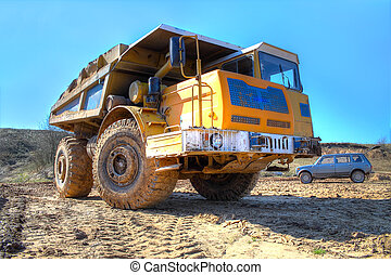 dumptruck - Tipper riding in an earthen pit at the blue sky...