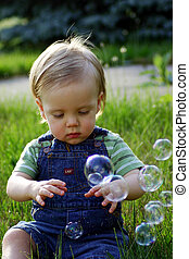 Baby in a field with bubbles