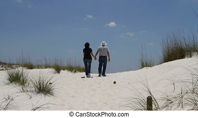 Couple Walking Up Dune - Mature retired couple holding hands...