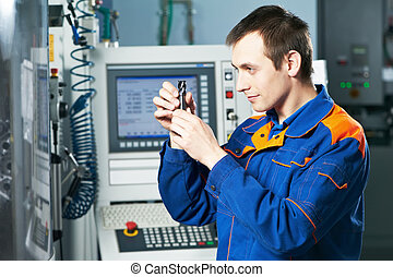 worker examining detail - mechanical technician checking...