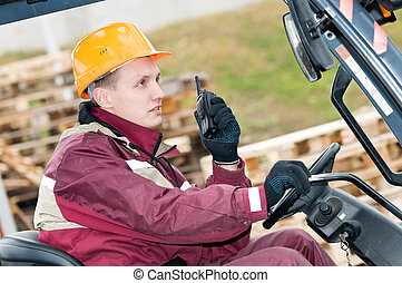 forklift driver with radio transmitter - man worker sitting...
