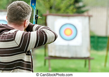 Archer aiming with bow - An archer with bow takes aim at a...