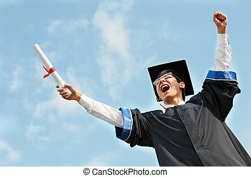 excited graduate student in gown with risen hands holding...