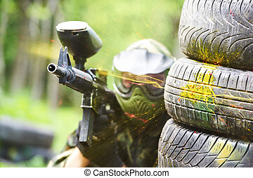 paintball player under gunfire - paintball sport player...