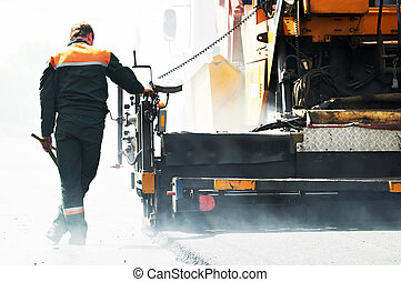 worker at asphalting works - Worker operating asphalt paver...