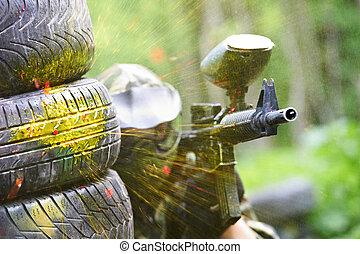 paintball player under gunfire - paintball sport player...