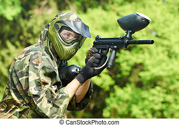 paintball player holding fire - paintball sport player in...