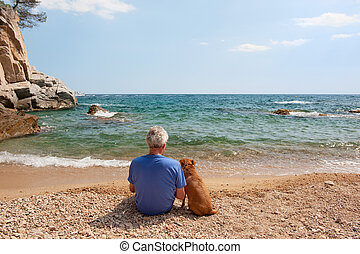 Man with his dog at the beach - Elderly man with his dog at...