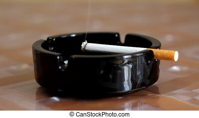 cigarette in an ashtray on the table