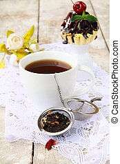 tea strainer with a fragrant black tea and cups in the...