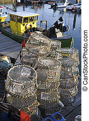 Lobster pots and a small fishing boat at Brighton Marina,...
