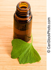 ginko biloba essential oil with fresh leaves - beauty...