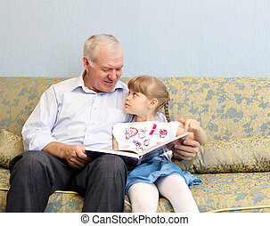 grandfather and granddaughter reading book