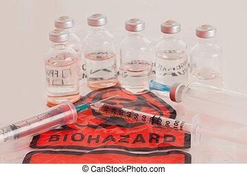 Bio Hazard, syringe with blood, glass vials on Bio Hazard...
