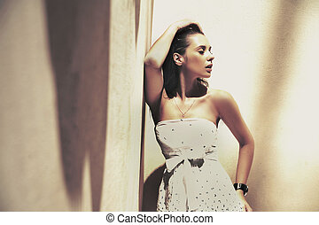Portrait of a young pretty brunette posin in a stylish...