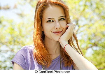 Beautiful redhead girl at the park in summer time.