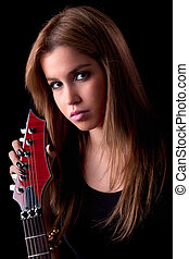 beautiful young woman with a electric guitar, on black, studio shot