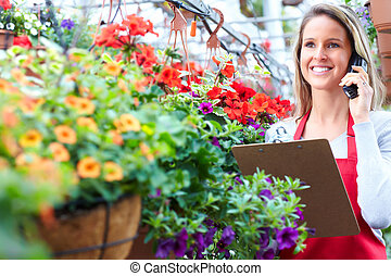 Gardening - Young woman florist working in the greenhouse
