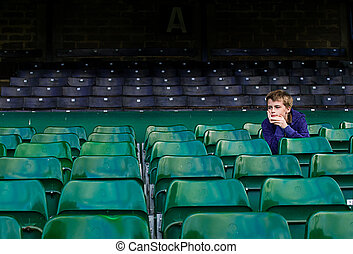 child in empty football stadium