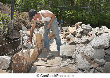 Building a rock wall - Mason building a rock wall from a...