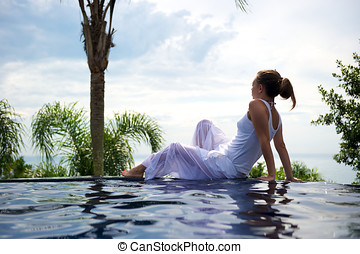 Paradise swimming pool - Woman relaxing in a paradise...