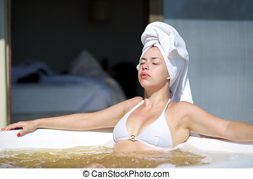 Woman relaxing in a jacuzzi in a resort in Porto Belo, Santa...