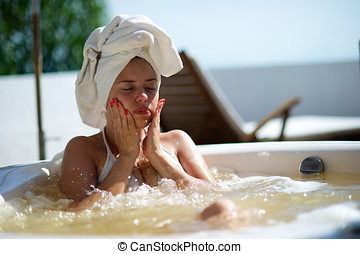 Woman relaxing in a jacuzzi in a resort in Porto Belo, Santa...