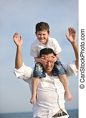 happy father and son have fun and enjoy time on beach -...
