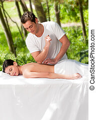 Outdoor Massage - A male masseur giving a massage to a woman...