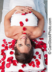 Smiling beautiful woman lying on a massage table with rose...