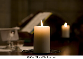 Candle On Altar - A candle on an altar is lit, illuminating...