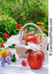 Red apples in basket and flowers in the garden