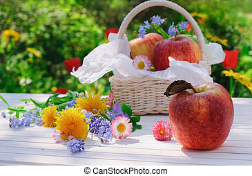 Red apples in basket with flowers in the garden