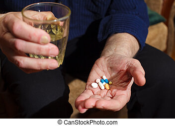 Pills And Water - close-up old mans hands with pills and...