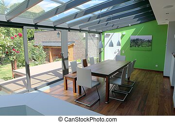 Conservatory with dining table on wooden floor