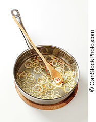 Frying onion rings in a pan - studio