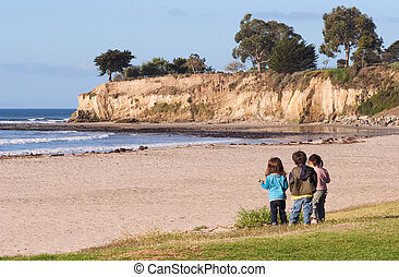 Exploring Children - Three youngsters looking at the Pacific...