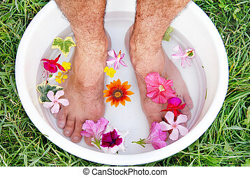 Male foot spa - male hairy feet in bowl with water and...