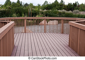 Board Walk trough green bushes - red wood board walk in a...